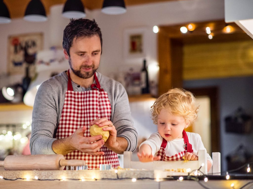dad and son are baking some cookies